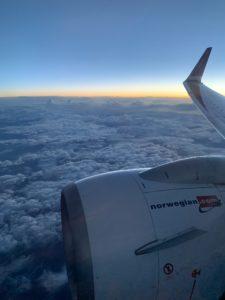 Utsikt fra et flyvindu med skyer og solnedgang.